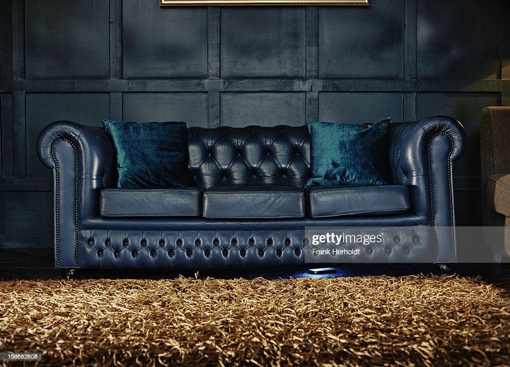 Phone ringing under sofa : Stock Photo