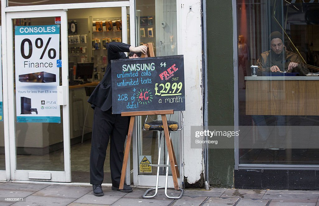 A phone shop employee adjusts a hand written sign advertising a Samsung smartphone mobile contract outside a store in Croydon, south London, U.K., on Monday, Feb. 10, 2014. Westfield Group, Australia's biggest mall operator, and Hammerson Plc won preliminary approval to rebuild the Whitgift Centre mall in south London as part of a project valued at about 1 billion pounds ($1.6 billion). Photographer: Jason Alden/Bloomberg via Getty Images