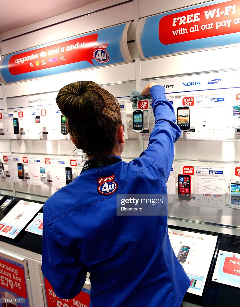A Phones 4u Ltd. employee cleans a smart phone display inside a Currys and PC World 2 in 1 store, operated by Dixons Retail Plc, in Manchester, U.K., on Tuesday, June 18, 2013. Dixons Retail Plc, the U.K.'s largest consumer-electronics retailer, said last month it will report annual pretax profit at the 'top end' of analysts' predictions after fourth-quarter revenue beat estimates on increased sales of tablets and services such as software tutorials. Photographer: Paul Thomas/Bloomberg via Getty Images