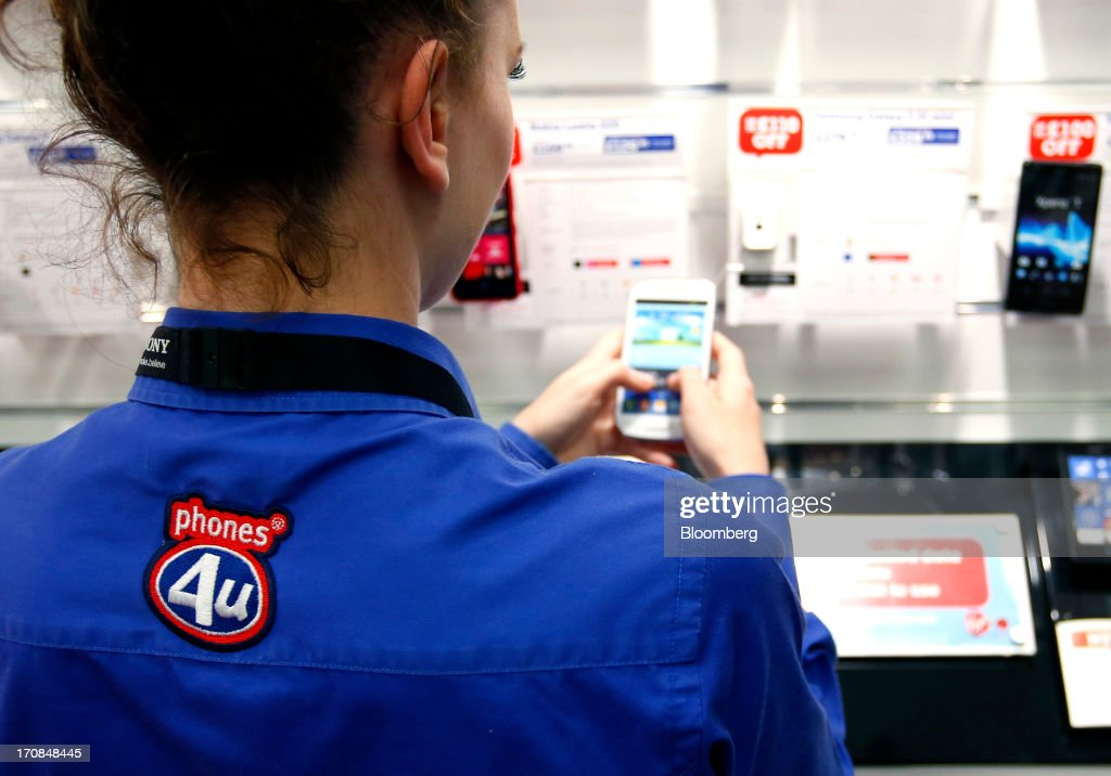 A Phones 4u Ltd. employee demonstrates a smart phone inside a Currys and PC World 2 in 1 store, operated by Dixons Retail Plc, in Manchester, U.K., on Tuesday, June 18, 2013. Dixons Retail Plc, the U.K.'s largest consumer-electronics retailer, said last month it will report annual pretax profit at the 'top end' of analysts' predictions after fourth-quarter revenue beat estimates on increased sales of tablets and services such as software tutorials. Photographer: Paul Thomas/Bloomberg via Getty Images