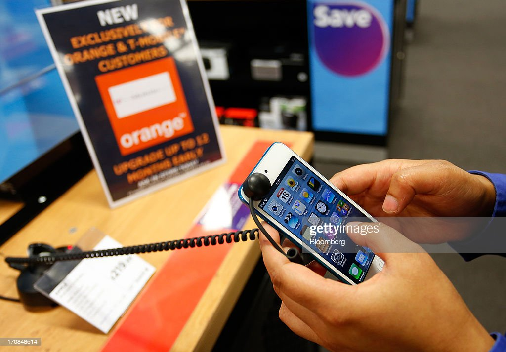 A Phones 4u Ltd. employee demonstrates an Apple Inc. iPod touch inside a Currys and PC World 2 in 1 store, operated by Dixons Retail Plc, in Manchester, U.K., on Tuesday, June 18, 2013. Dixons Retail Plc, the U.K.'s largest consumer-electronics retailer, said last month it will report annual pretax profit at the 'top end' of analysts' predictions after fourth-quarter revenue beat estimates on increased sales of tablets and services such as software tutorials. Photographer: Paul Thomas/Bloomberg via Getty Images
