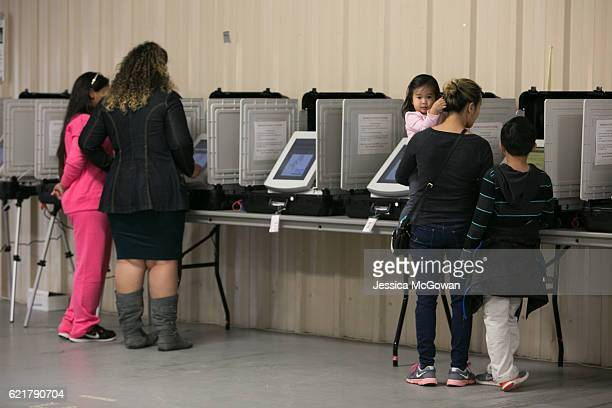 Phonexay Do casts her vote with her children Ana and Tyler at the Gwinnett County Fairgrounds on November 8 2016 in Lawrenceville Georgia After a...