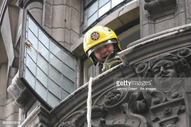 Photo A firefighter shouts to colleagues down below from the third floor of a building in Knightsbridge West London where a fire had earlier broken...