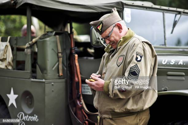 Photo A man in period military clothing searches the internet on his smart phone while leaning on a WWII Jeep at the WWII Weekend at Castle Drogo in...
