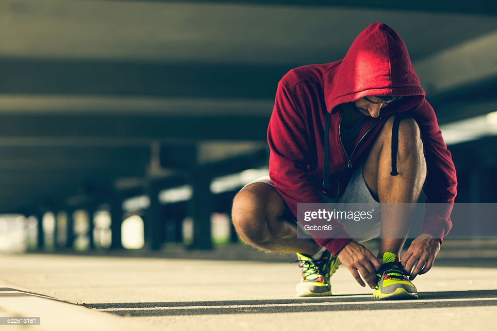Photo af an athletic man tying his shoelace : Stock Photo