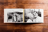 Photo album with black-and-white pictures of senior couple in love. Studio shot on wooden background.