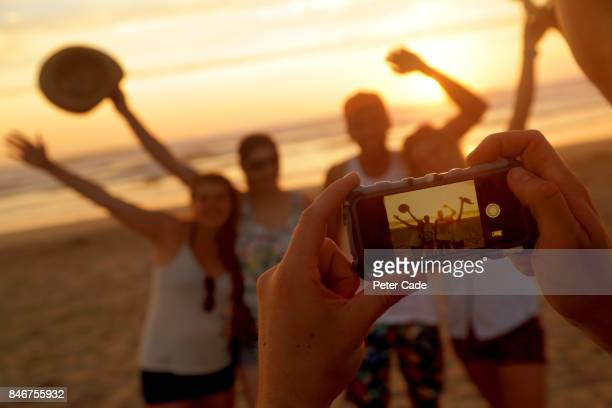 Photo being taken of group of young adults on beach at sunset