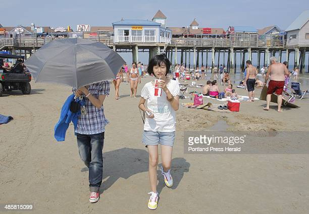 Photo by Gregory Rec/Staff Photographer Jun Yu Luo left under umbrella and Ri Xin Cao walk on Old Orchard Beach on Wednesday The girls were visiting...