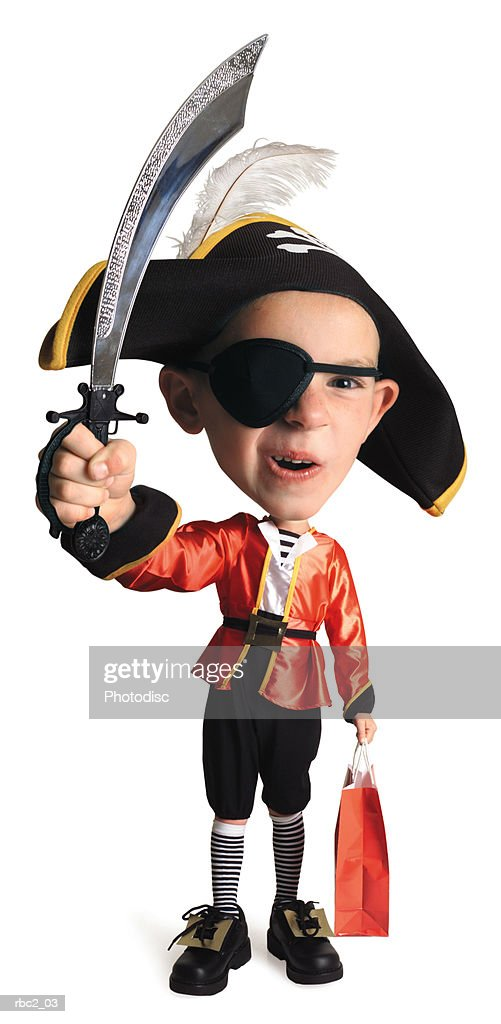 photo caricature of a caucasian boy in his pirate costume, as he waves his sword in the air with one hand, and a trick or treat bag in the other : Stock Photo