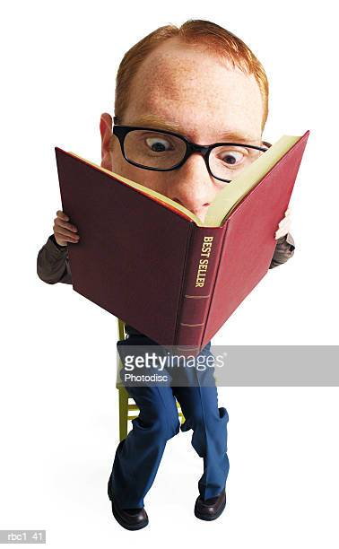 photo caricature of a young caucasian man with red hair and glasses who sits and intensly reads a very large book