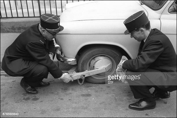 Photo datée du 01 février 1968 de deux policiers posant un 'sabot de Denver' sur un véhicule mal garé une invention importée des EtatsUnis utilisée...