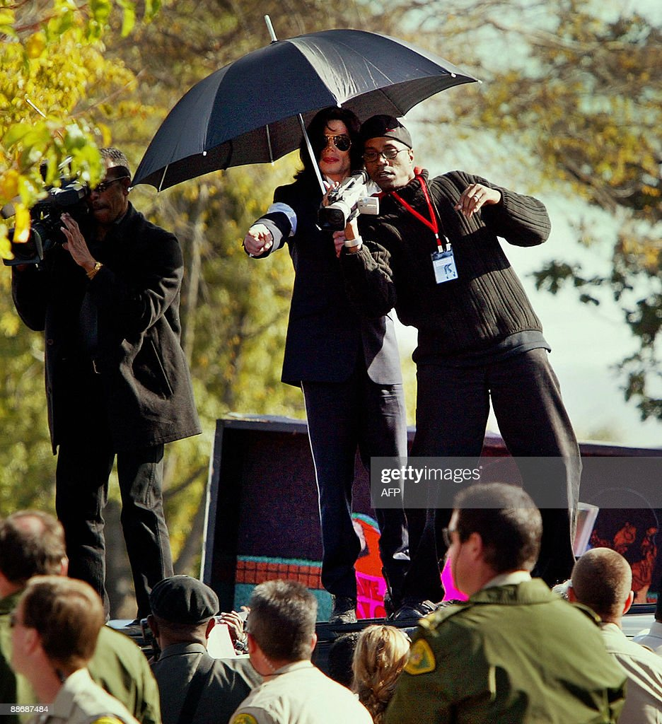 Photo dated January 16, 2004 shows US pop star <a gi-track='captionPersonalityLinkClicked' href=/galleries/search?phrase=Michael+Jackson&family=editorial&specificpeople=70011 ng-click='$event.stopPropagation()'>Michael Jackson</a> directing his videographers to photograph his fans as they stand on top of the singer's limousine following his arraignment on child molestation charges, outside the courthouse in Santa Maria, California. Jackson died on June 25 after suffering a cardiac arrest, multiple US media outlets reported, sending shockwaves around the entertainment world.