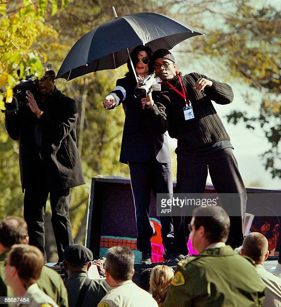 Photo dated January 16 2004 shows US pop star Michael Jackson directing his videographers to photograph his fans as they stand on top of the singer's...