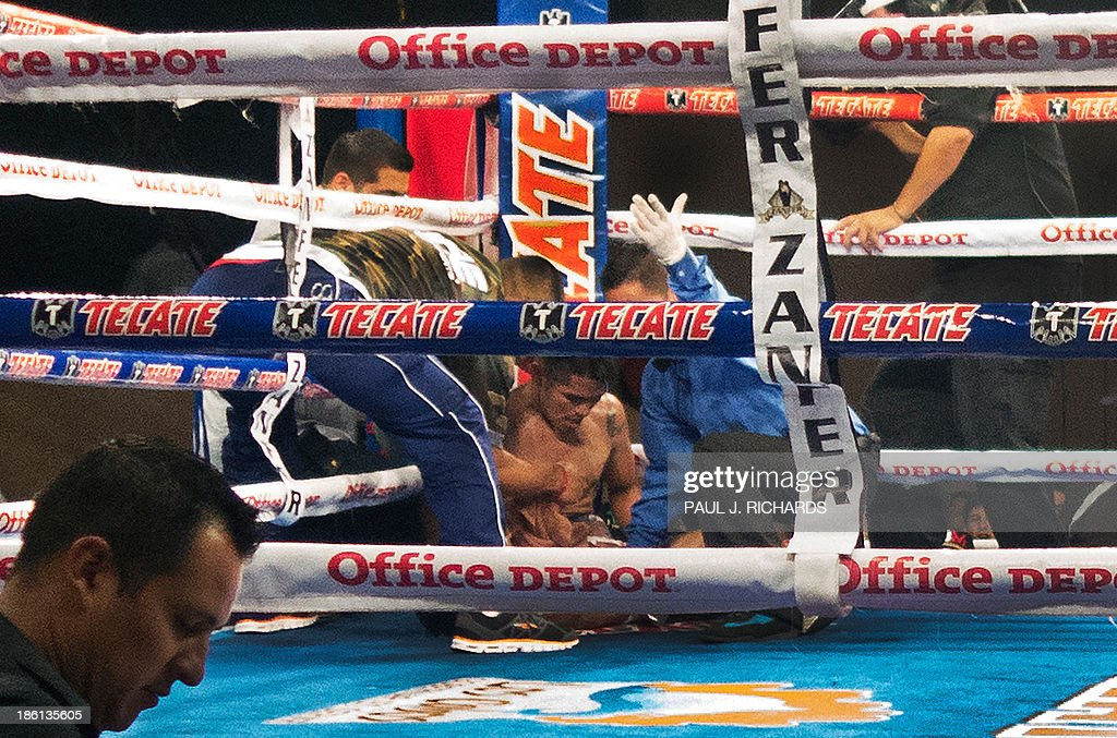 Photo dated October 19, 2013 shows Mexican boxer Francisco 'Frankie' Leal being evaluated by the referee after an 8th round set of body shots and two to the head by opponent Raul Hirales in Cabo San Lucas. Leal, 26, was taken away by stretcher shortly after and died on October 22 from a cerebral contusion in a San Diego, California, hospital. Leal, whose nickname was 'The Little Soldier' had 29 wins, 8 lossses, and 3 draws. AFP PHOTO/Paul J. Richards
