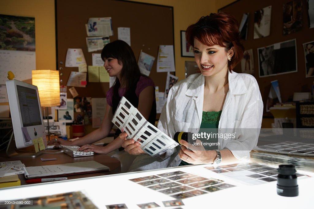 Photo editor working at lightbox : Stock Photo