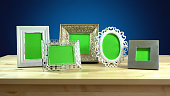 Row of photo frames with blank green screens in elegant table interiors display