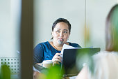 Young Maori businesswoman in office setting having discussion with colleague