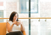 Young Maori businesswoman relaxes on a coffee break in an open plan office setting in New Zealand