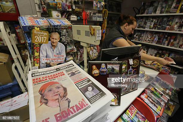 A photo illustration of Hillary Clinton Democratic Party leader sits on the cover of 'Sovershenno sekretno' newspaper beside a magazine cover showing...