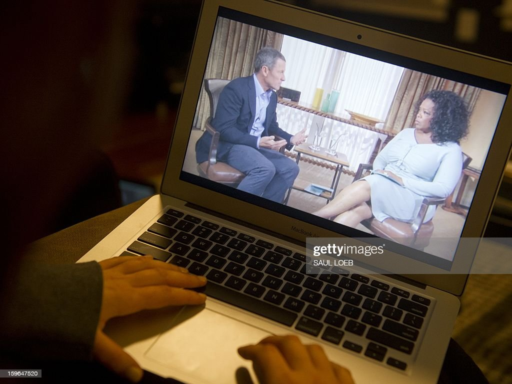 Photo illustration showing a woman watches on her computer as Oprah Winfrey interviews cyclist Lance Armstrong about doping while competing professionally in the sport, as seen from Washington, DC, on January 17, 2013. The interview will run in two parts on Winfrey's OWN cable network and website. AFP PHOTO / Saul LOEB