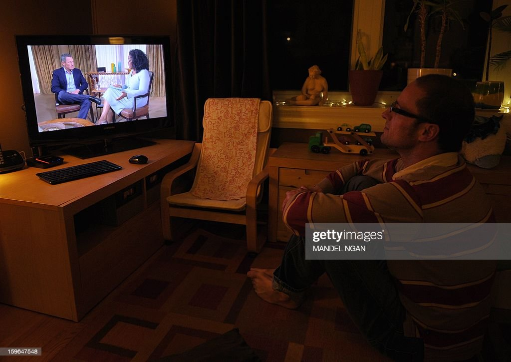 A photo illustration shows a man watching a TV showing disgraced cycling star Lance Armstrong being interviewed by Oprah Winfrey on January 17, 2013 in Kensington, Maryland. Armstrong said in the interview that he was 'sorry' for taking performance-enhancing drugs during his career and that it was a mistake. AFP PHOTO/Mandel NGAN