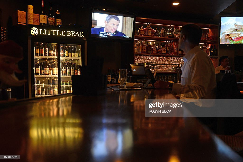 A photo illustration shows a man watching a TV showing disgraced cycling star Lance Armstrong being interviewed by Oprah Winfrey on January 17, 2013 is seen in a bar in downtown Los Angeles. AFP PHOTO / Robyn BECK