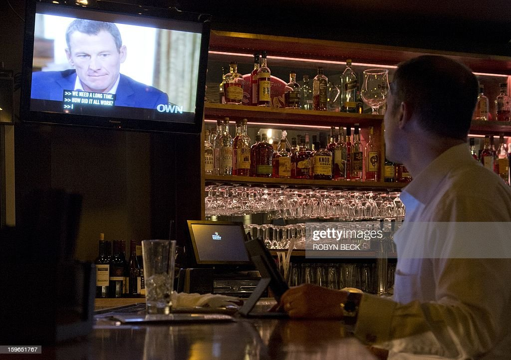 A photo illustration shows a man watching a TV showing disgraced cycling star Lance Armstrong with Oprah Winfrey is seen in a bar in downtown Los Angeles January 17. 2013. During the interview Lance Armstrong admited doping while competing professionally in the sport.. AFP PHOTO / Robyn Beck
