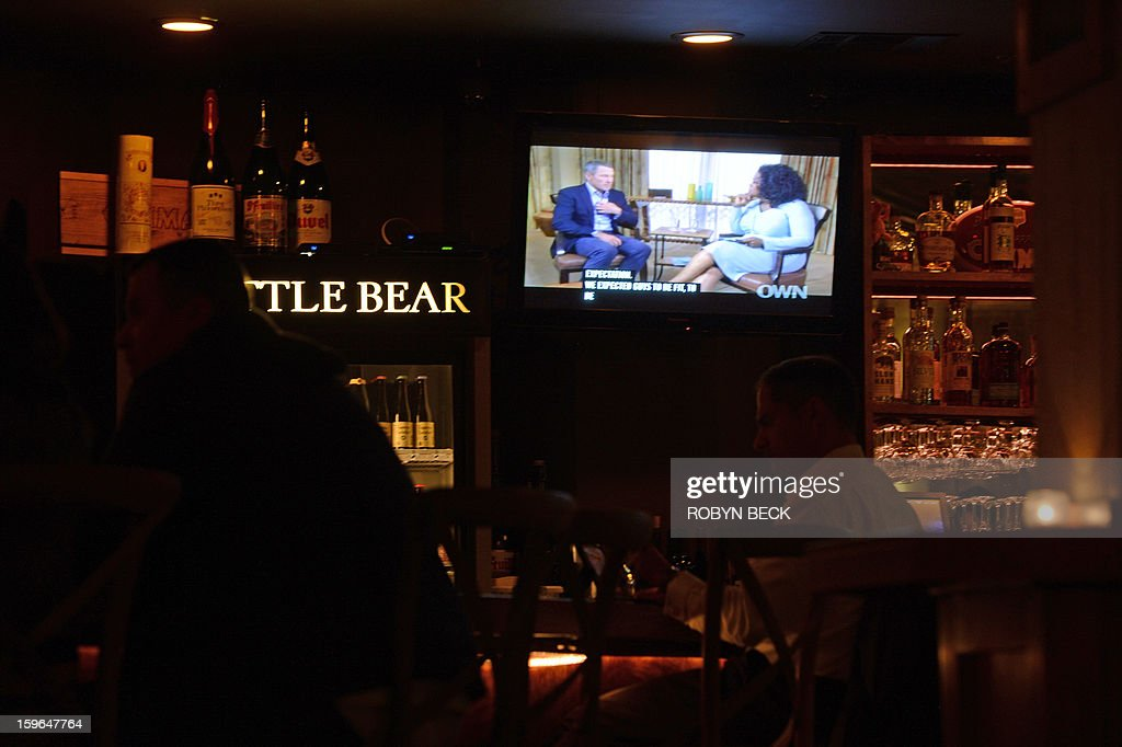 A photo illustration shows a TV showing disgraced cycling star Lance Armstrong being interviewed by Oprah Winfrey on January 17, 2013 in a bar in downtown Los Angeles. AFP PHOTO / Robyn BECK