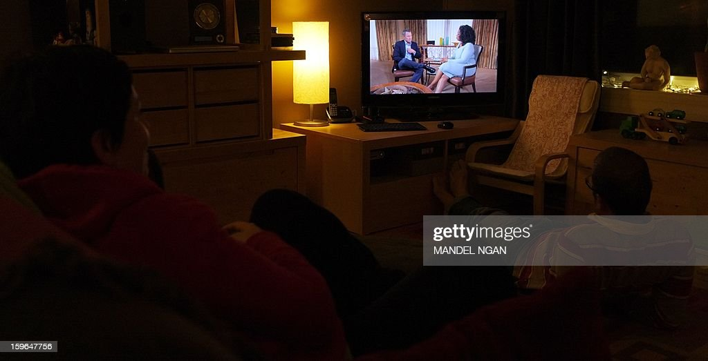 A photo illustration shows people watching a TV showing disgraced cycling star Lance Armstrong (L) being interviewed by Oprah Winfrey on January 17, 2013 in Kensington, Maryland. Armstrong said in the interview that he was 'sorry' for taking performance-enhancing drugs during his career and that it was a mistake. AFP PHOTO/Mandel NGAN