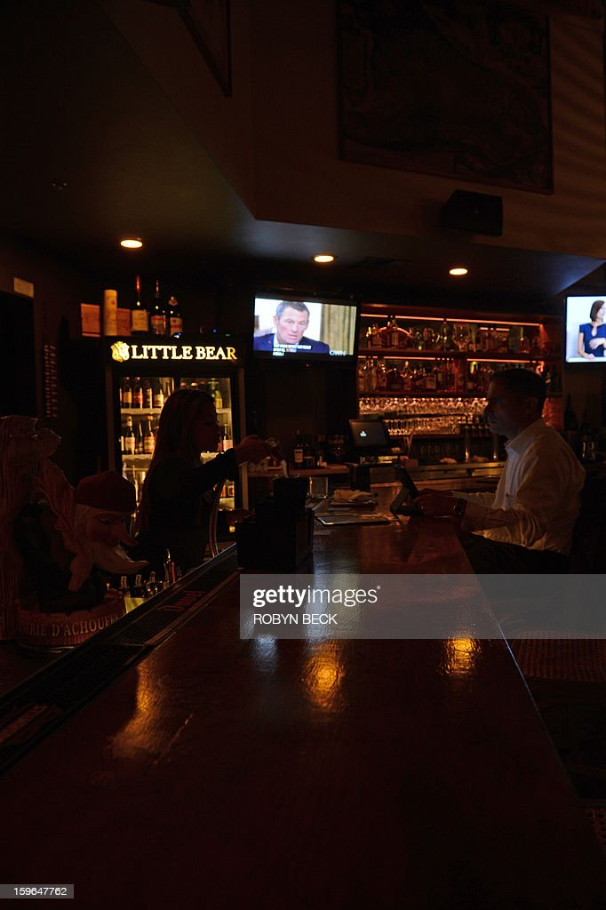 A photo illustration shows people watching a TV showing disgraced cycling star Lance Armstrong being interviewed by Oprah Winfrey on January 17, 2013 in a bar in downtown Los Angeles. AFP PHOTO / Robyn BECK