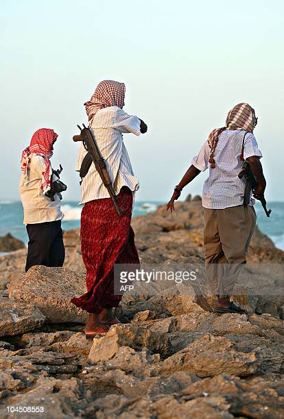 Photo made on January 4 2010 shows armed Somali pirates keeping vigil on the coastline at Hobyo town in northeastern Somalia where Greek cargo ship...