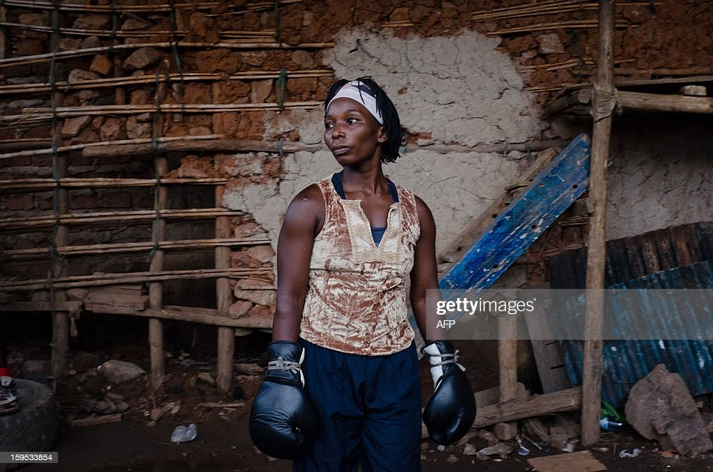 Photo made on November 13, 2012 shows female boxer Maureen inside the Rhyno gym at the Kataanga slum of Kampala where Helen and Diana Turyanabo, both professional female Ugandan boxers practice their skill. Helen, 23, along with her younger sister Diana, 20, living in a trash ridden slum area, are two young women who stand out amongst their neighbours as they both are professional boxers, literally trying to fight their way out of poverty. After a man tried to rape Helen, the older of the two sisters, it inspired her to learn how to fight inorder defend herself, and despite recently winning a medal in an East African Regional Championship, Helen and Diana still have to collect garbage to sell to get money for food for themselves and nearly 20 other people, cramped into two rooms with no water or electricity. AFP PHOTO/Michele Sibiloni.