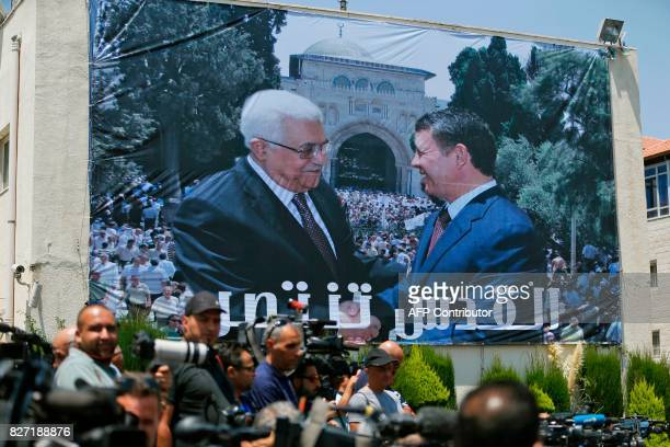 A photo montage of Jordan's King Abdullah II and Palestinian president Mahmud Abbas shaking hands in front of the AlAqsa mosque compound is seen on a...