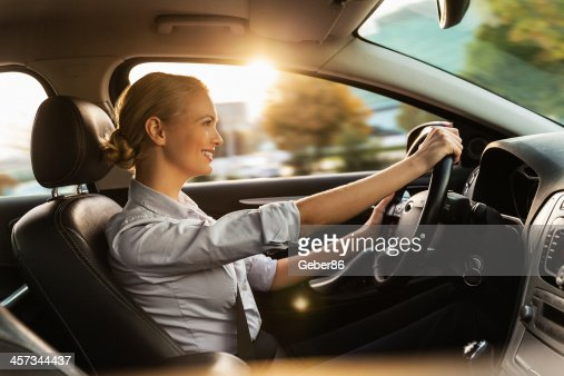 Photo of a beautiful smiling young businesswoman driving car