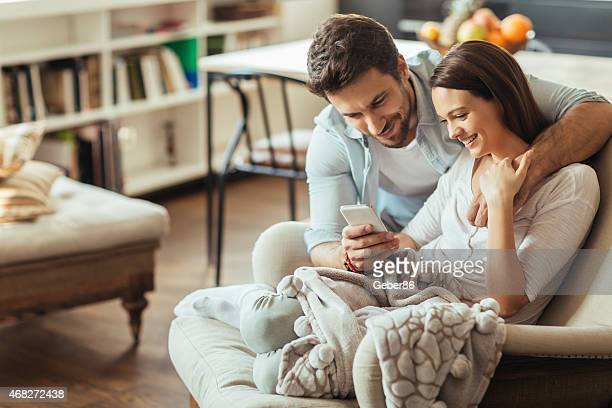 Photo of a beautiful young couple looking at smartphone