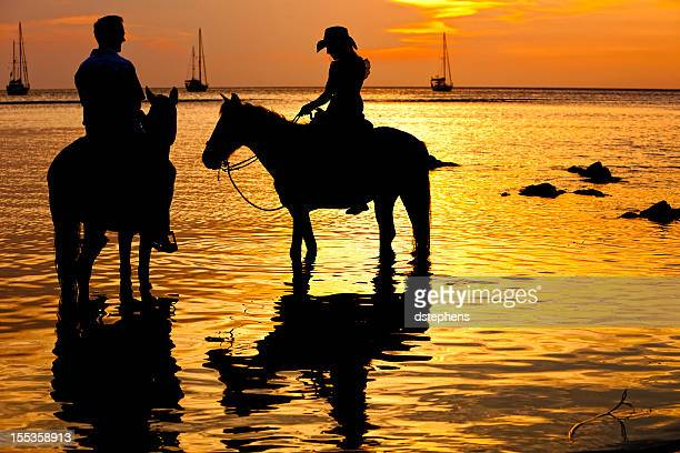 Photo of a couple riding horses at sunset on the beach