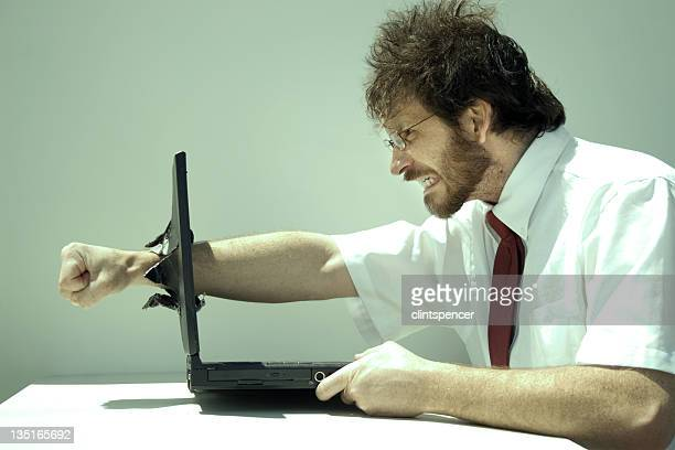 Photo of a frustrated man punching clean through his laptop