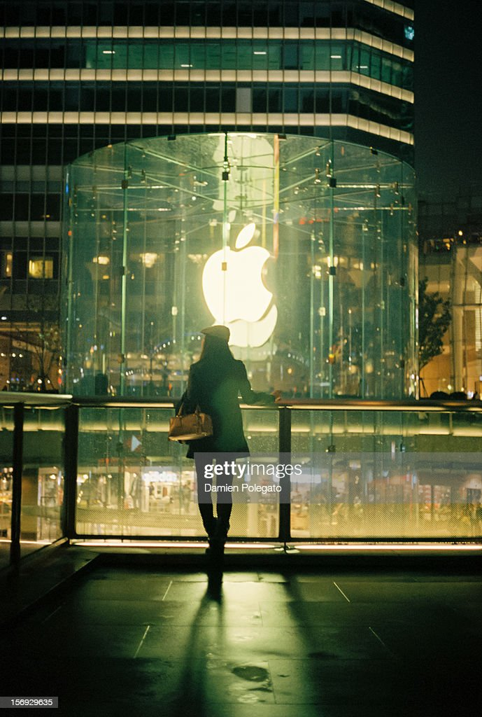 Photo of a girl standing in front of the Apple store located in Shanghai Business district, Lujiazui in Pudong.