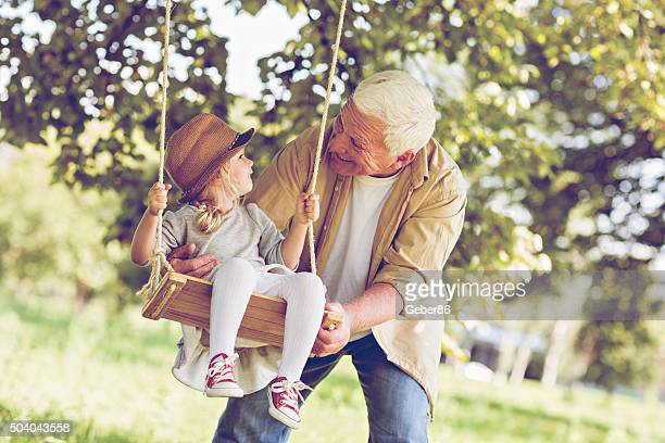 Photo of a grandfather and his granddaughter on swing