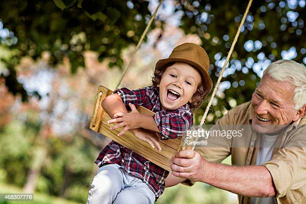 Photo of a grandfather and his grandson on swing