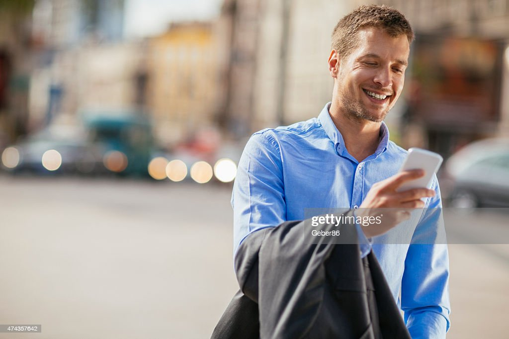 Photo of a handsome businessman using smart phone : Stock Photo