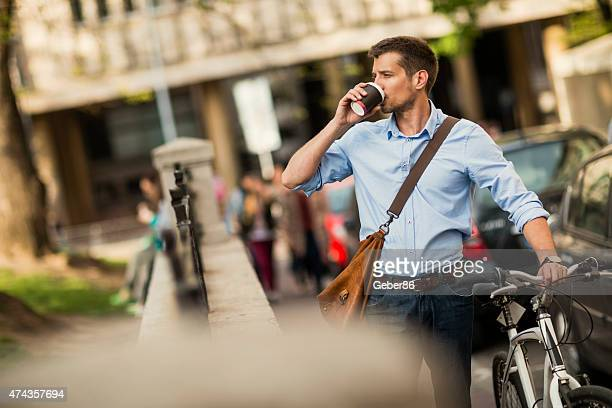 Photo of a handsome man having coffee while leading bike