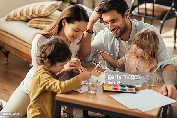 Photo of a happy family painting with water colors