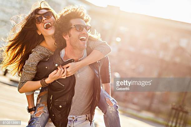 Photo of a happy laughing young couple in city