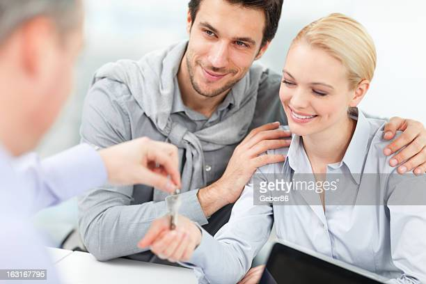 Photo of a happy young couple receiving new house keys