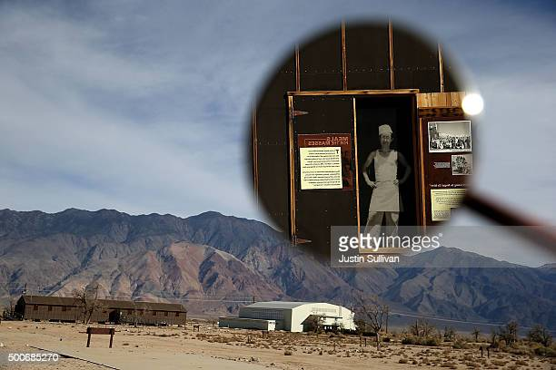 A photo of a Japanese kitchen worker is seen in the mirror of a vintage outside of a replica of an internment camp mess hall at Manzanar National...