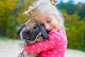 Five-year-old beautiful girl embraces the favourite rabbit
