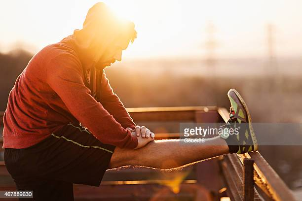Photo of a man stretching after run