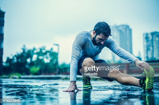 Photo of a man stretching in the rain
