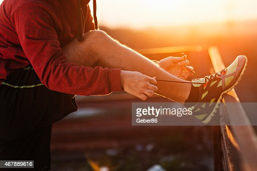 Photo of a man tying his shoe lace